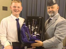 Liam Nicolson receives his prize pipe (sponsored by McCallum Bagpipes) from National Piping Principal Brett Tidswell.