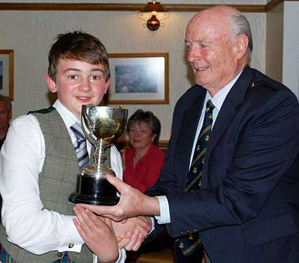 Finlay Cameron receives his trophy from James MacLean at the 2016 Young Piper of the Year competition.