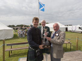 William Rowe, from New Zealand, won the John Murray Memorial Cup for March and the Gordon Asher Memorial Cup for Strathspey and Reel at the Halkirk Highland Games.He is seen here receiving one of his trophies from piping judge John Macrae, (right), while piping stewart Charlie Swanson holds the other trophy.Photo: Robert MacDonald/Northern Studios