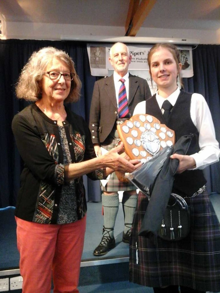 Anne Lore presents Hazel White with the David Green Shield, awarded to the overall winner of the 18 & Under category. trophy.