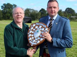 Piping Secretary, Murray Henderson presents overall Open champion, Pipe Major Ben Duncan with the Angus Hotel Challenge Shield.
