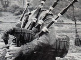 Pipe Major George MacKenzie piping in front of Eilean Donan Castle on the shores of Loch Duich.